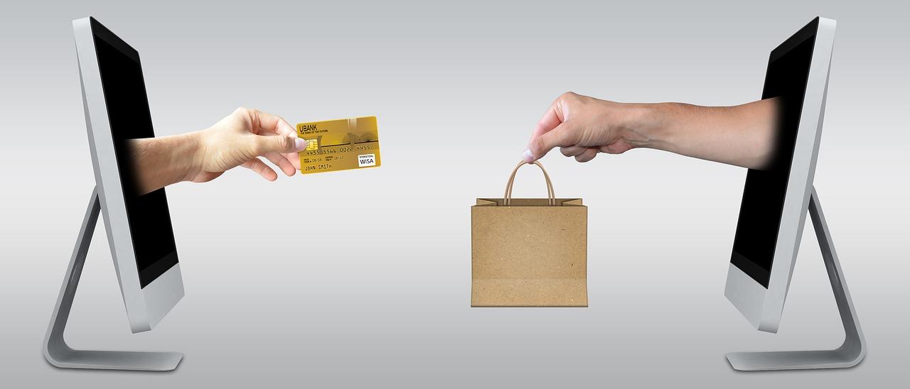 Kaksi kättä. Toinen ojentaa luottokorttia, toinen ostoksia.