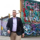 Jesse Uitto kävelee, graffiteja taustalla.